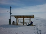 A bus shelter at the top of a snowy mountain pass