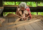 Old Thai villager making brooms